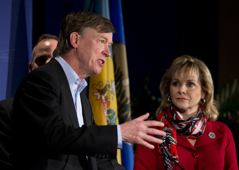 Colorado Gov. John Hickenlooper, seen with National Governors Association Vice Chairman Gov. Mary Fallin of Oklahoma, right, and  NGA Chairman Gov. Jack Markell of Delaware, obscured, speak at the opening news conference of the NGA Winter Meeting in Washington, Saturday, Feb. 23, 2013. The nation's governors say their states are threatened if the automatic, across-the-board budget cuts, known as the sequester, take effect March 1.  (AP Photo/Manuel Balce Ceneta)
