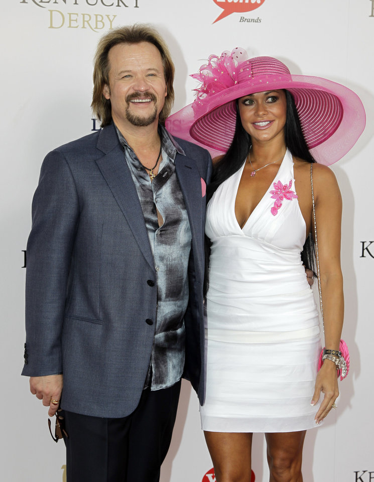 Photo - Country singer Travis Tritt arrives with a guest for the 138th Kentucky Derby horse race at Churchill Downs Saturday, May 5, 2012, in Louisville, Ky. (AP Photo/Darron Cummings)  ORG XMIT: DBY158