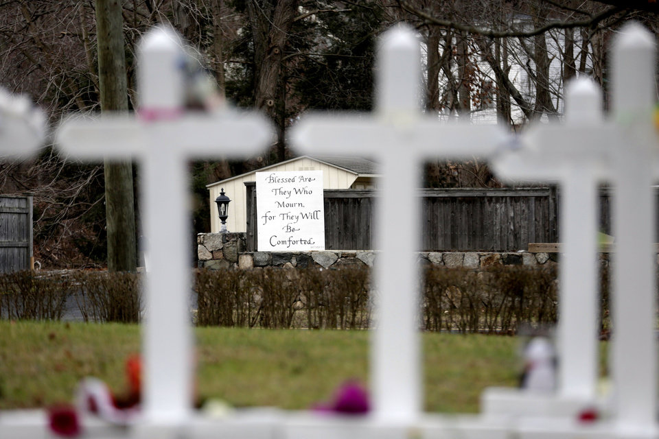 A large sign is displayed across the street from crosses bearing the names of the Newtown shooting victims in the Sandy Hook village of Newtown, Conn., Saturday, Dec. 22, 2012.   The funerals for the victims of the school shooting are wrapping up after a wrenching week of farewells. Twenty children and six adults were killed at Sandy Hook Elementary School on Dec. 14.  Adam Lanza, the lone gunman, killed his mother before going on the rampage and then committed suicide. (AP Photo/Seth Wenig)