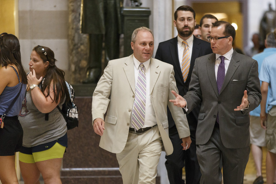 Photo - Rep. Steve Scalise, R-La., the incoming House GOP whip, walks between tourists and reporters in Statuary Hall on the way to the House chamber, at the Capitol in Washington, Wednesday, July 30, 2014. Republicans pushed a divided House Wednesday toward a campaign-season lawsuit against President Barack Obama, accusing him of deliberately exceeding the bounds of his constitutional authority. Democrats have branded the effort a political charade aimed at stirring up Republican voters for the fall congressional elections.  (AP Photo/J. Scott Applewhite)