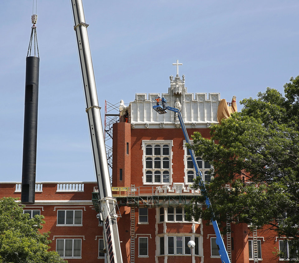 Photo - Historic Benedictine Hall, the centerpiece building on the campus of St. Gregory's University in Shawnee,  lost all four of its iconic turrets in a 5.6-magnitude earthquake in 2011. Restoration to the building began in March. In an effort to make the future  turrets earthquake proof, the new frames are 56 feet long and are constructed of steel. Each one weighs 16,000 pounds. The frames were lifted by a large crane into their rightful places atop the fifth story of Benedictine Hall. They will later be bricked and receive decorative molding. It took about an hour to unload, lift and secure the new turret on top of the building, Friday morning, June 14, 2013. The other three turrets will be installed in coming weeks, a university spokesman said. Photo  by Jim Beckel, The Oklahoman.