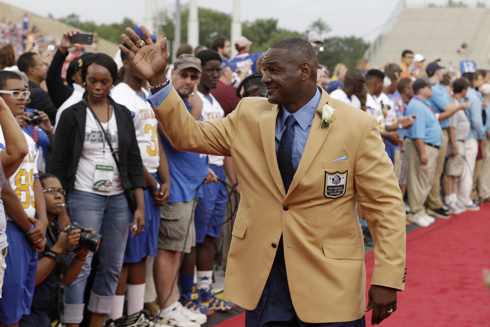 Photo - Hall of Fame inductee Derrick Brooks waves to fans as he is introduced during the Pro Football Hall of Fame enshrinement ceremony Saturday, Aug. 2, 2014, in Canton, Ohio. (AP Photo/Tony Dejak)
