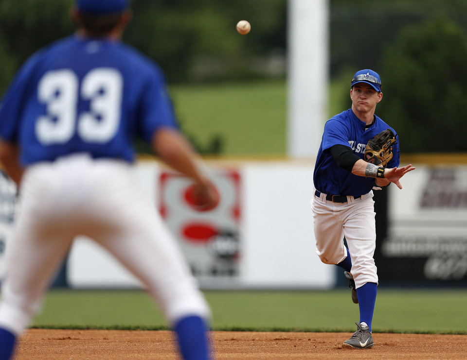 Photo - Casey Bowlan, of Shawnee, throws a ball to Austin O'Brien, of Owasso, during the large school All-State Baseball game between East and West at Johnson Stadium at Oral Roberts University in Tulsa, Okla., Tuesday, July 30, 2013. GARETT FISBECK/Tulsa World