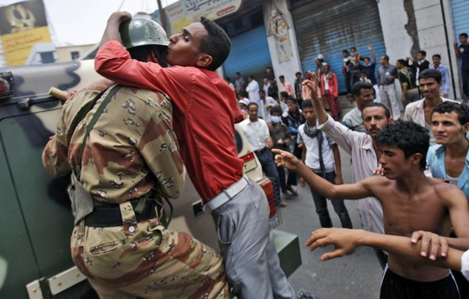 Photo -  An anti-government protestor kisses a Yemeni army soldier during a demonstration demanding the resignation of Yemeni President Ali Abdullah Saleh, in Taiz,Yemen, Thursday, April 7, 2011. The Yemeni opposition has welcomed an offer by Arab Gulf states to mediate between the president and opposition protesters who have demanded Ail Abdullah Saleh step down after 32 years in power. (AP Photo/Hani Mohammed) ORG XMIT: XMM110