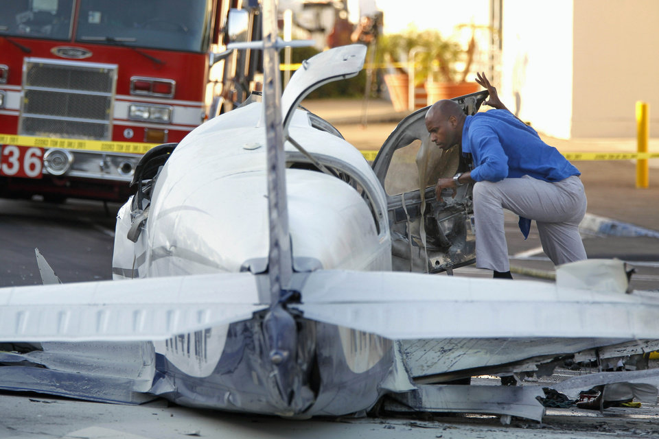 Photo - An aviation safety inspector looks inside the cockpit of a small airplane after it crashed in a shopping center parking lot Wednesday afternoon, July 30, 2014, in San Diego. One woman was killed and another seriously injured, a fire spokesman said. (AP Photo/UT San Diego, Hayne Palmour IV) NO SALES  MANDATORY CREDIT  TV OUT  MAGS OUT
