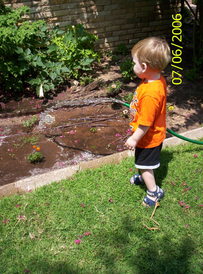 "My grandson, Justin Ryan helping ""Ganny"" water the gardens! Community Photo By: Teresa Chapman a.k.a. ""Ganny"" Submitted By: Teresa, Bethany"