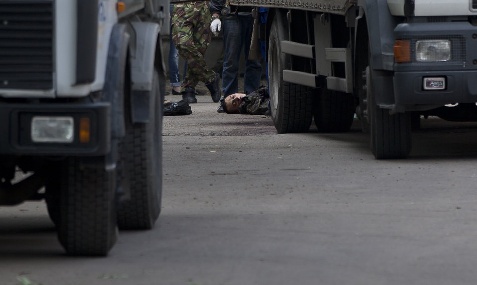 Photo - The body of a pro-Russian gunman killed during clashes with Ukrainian government forces around the airport lies on the pavement outside a city morgue in Donetsk, Ukraine, Tuesday, May 27, 2014. The eastern city of Donetsk was in turmoil Tuesday a day after government forces used fighter jets to stop pro-Russia separatists from taking over the airport. Dozens were reported killed and the mayor went on television to urge residents to stay indoors. (AP Photo/Vadim Ghirda)