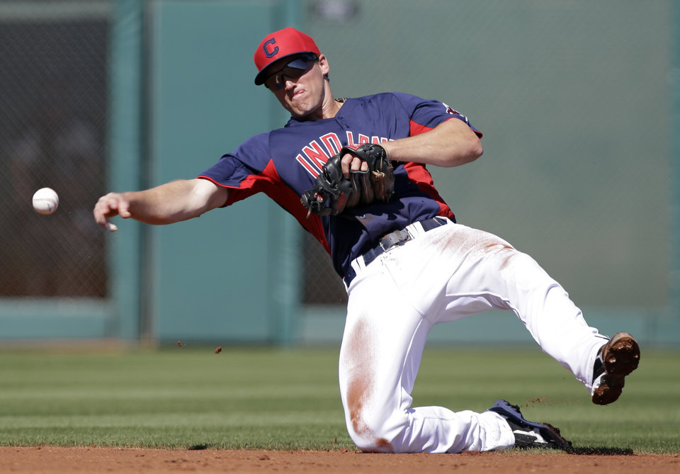 Cleveland Indians second baseman Cord Phelps throws from his knees but can't get Chicago White Sox's Gordon Beckham on an infield single in the third inning of a spring training baseball game Friday, March 1, 2013, in Goodyear, Ariz. (AP Photo/Mark Duncan)