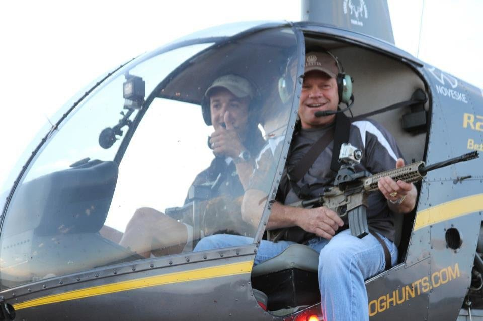 Photo - Hunter Dustin Ellermann is shown with his rifle in a helicopter during a recent hunt in Texas. Photo provided
