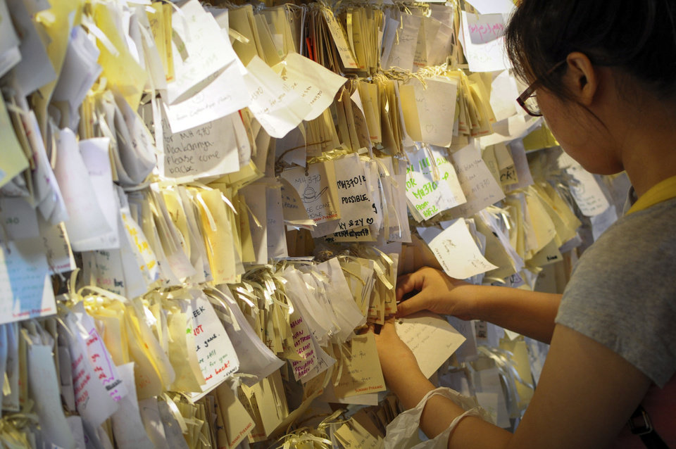 Photo - A woman ties a message card for passengers onboard the missing Malaysia Airlines Flight 370 at a shopping mall in Petaling Jaya, near Kuala Lumpur, Malaysia, Thursday, April 10, 2014. With hopes high that search crews are zeroing in on the missing Malaysian jetliner's crash site, ships and planes hunting for the aircraft intensified their efforts Thursday after equipment picked up sounds consistent with a plane's black box in the deep waters of the Indian Ocean. (AP Photo)