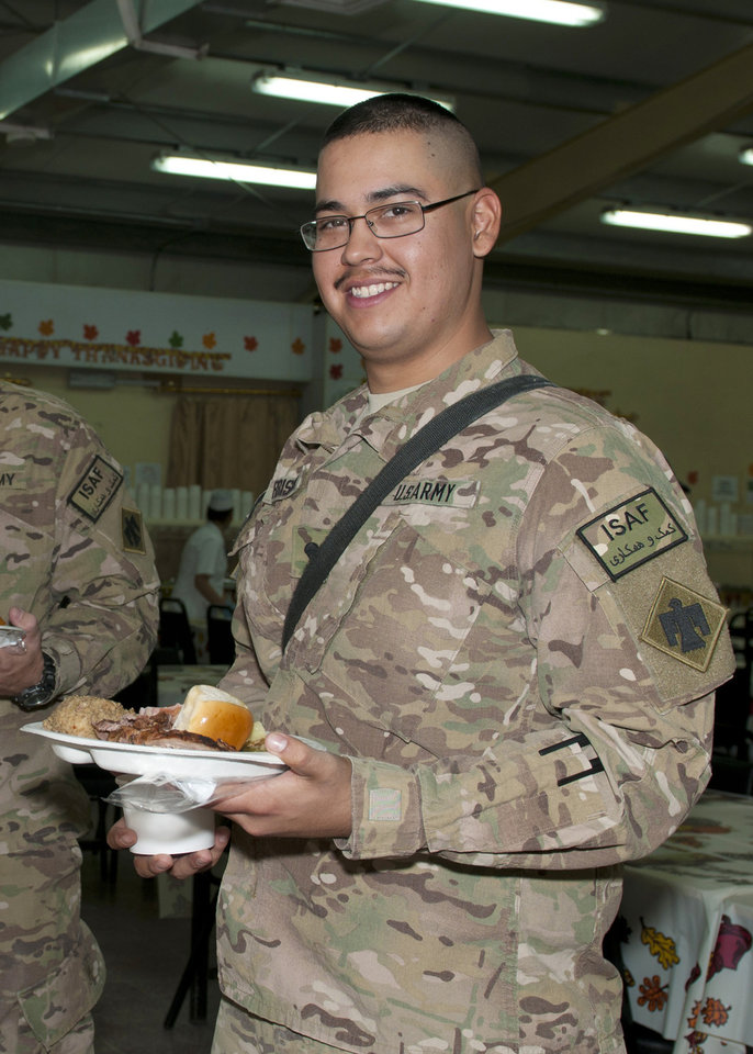 "LAGHMAN PROVINCE, Afghanistan - This Thanksgiving, members of the 45th Infantry Brigade Combat Team along with other units stationed at Forward Operating Base Gamberi, were able to enjoy the traditional meal with their military family and friends for both lunch and dinner. Spc. James Morrions of Moore, Okla. is a member of Headquarters and Headquarters Co., 700th Brigade Support Battalion, 45th IBCT. When asked how he would be spending Thanksgiving if he were home, Morrison replied, ""Usually my family and I go to two different houses. The smells (at the dining facility) reminded me a lot of home.""  U.S. Army photo by Maj. Lindy White, Task Force Thunderbird Public Affairs"