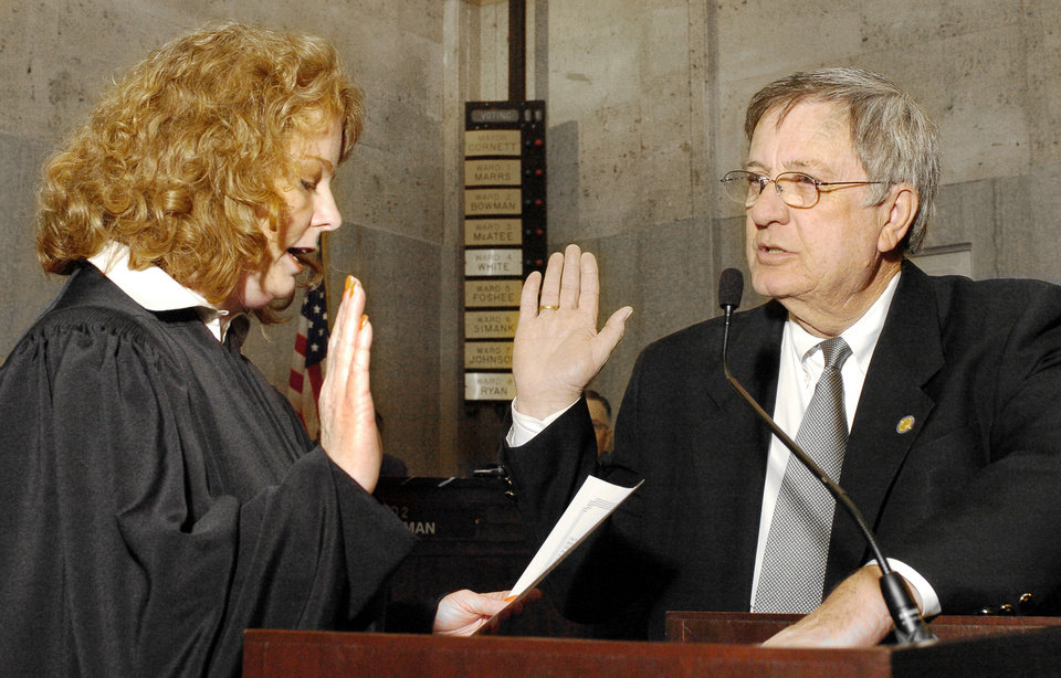 Photo - Pete White, at right, is sworn in as Ward 4 Oklahoma City councilman by Okla. County District Judge Barbara Swinton, at left, during the Oklahoma City council meeting Tuesday morning, April 12, 2005, at City Hall in downtown Okla. City. Staff photo by Paul B. Southerland