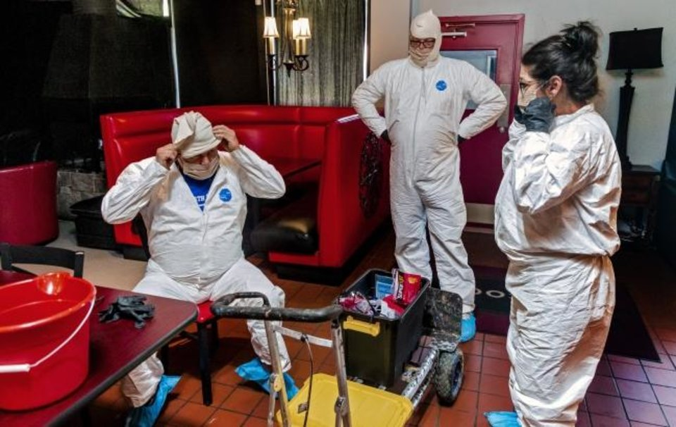 Photo -  Joe Barnes, owner of Safe Spray Services, Wade Smallwood and Jenifer Minardi, from left, put on their safety gear as they prepare to sprays disinfectant at Rococo restaurant on Friday in Oklahoma City. Barnes turned his grease traps cleaning service to a COVID-19 deep-cleaning service, that includes disinfectant spay, clean-up and UV ray treatment, to contribute to the pandemic response and keep his employees paid.  [Chris Landsberger/The Oklahoman]