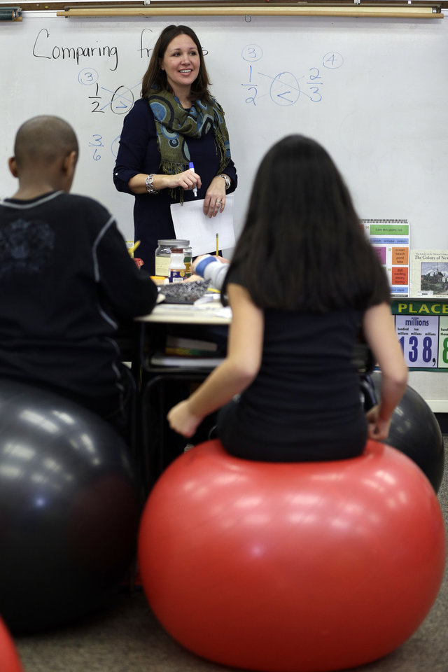 Photo - Robbi Giuliano teaches her fifth grade class as they sit on yoga balls at Westtown-Thornbury Elementary School Monday, Feb. 4, 2013, in West Chester, Pa.   By making the sitter work to stay balanced, the balls force muscle engagement and increased blood flow, leading to more alertness.  (AP Photo/Matt Rourke)