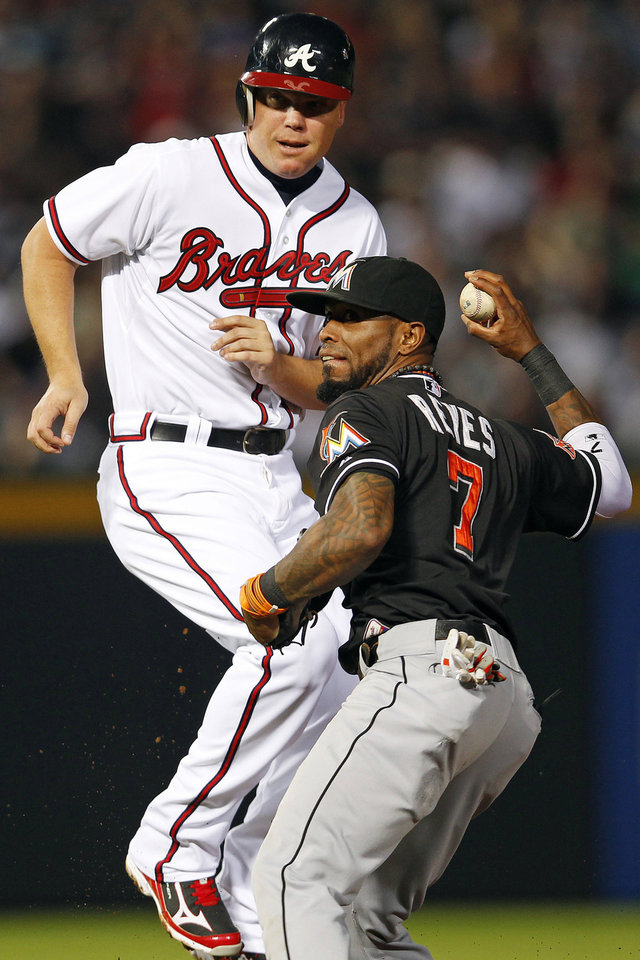 Photo -   Miami Marlins shortstop Jose Reyes (7) throws to first base after tagging out Atlanta Braves' Chipper Jones (10) on a ground ball from Freddie Freeman (5) in the second inning of a baseball game in Atlanta, Thursday, Sept. 27, 2012. (AP Photo/John Bazemore)