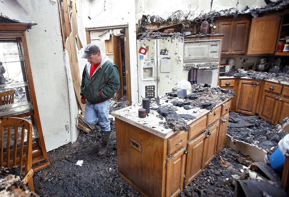 Photo - Charles Collier walks through his home Friday as he looks over his destroyed home that was consumed by wildfires in Midwest City.  Photo by Chris Landsberger, The Oklahoman