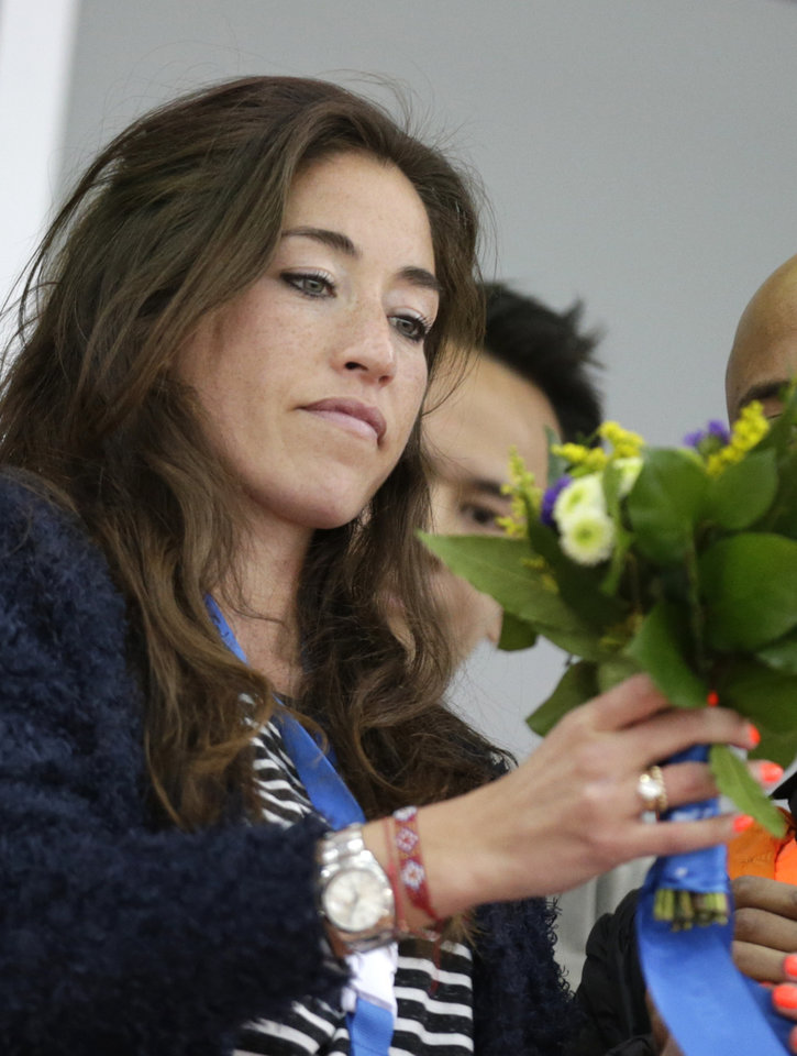 Photo - Naomi van As, Dutch hockey player and girlfriend of Sven Kramer of the Netherlands, holds flowers given to her by Kramer after he won gold in the men's 5,000-meter speedskating race at the Adler Arena Skating Center at the 2014 Winter Olympics in Sochi, Russia, Saturday, Feb. 8, 2014. (AP Photo/Matt Dunham)