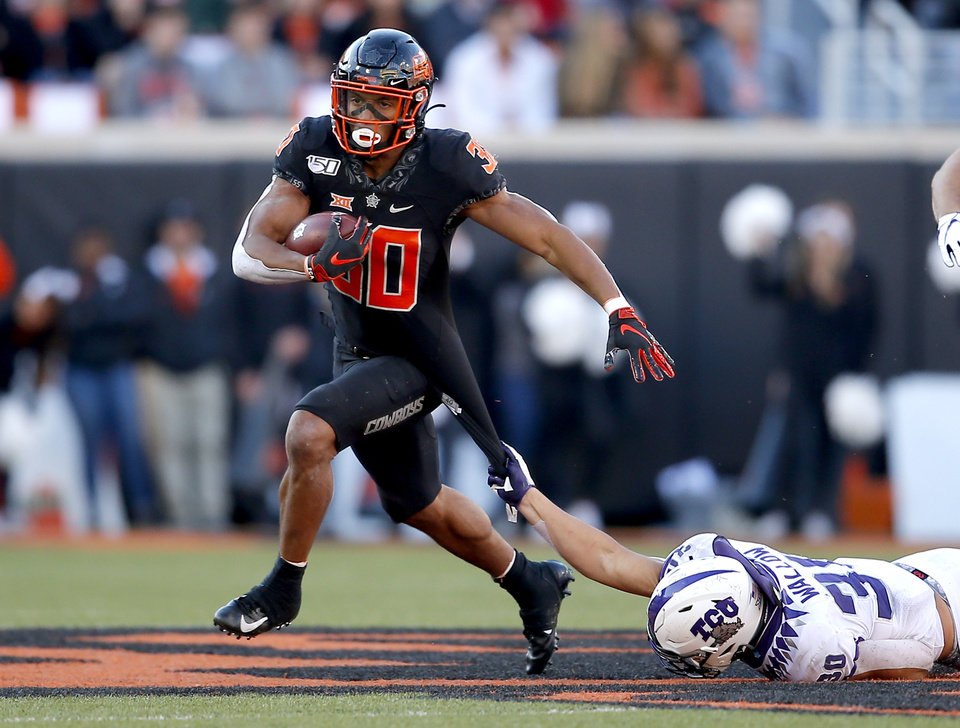 Photo - TCU's Garret Wallow (30) tries to bring down Oklahoma State's Chuba Hubbard (30) in the fourth quarter during the college football game between the Oklahoma State University Cowboys and the TCU Horned Frogs at Boone Pickens Stadium in Stillwater, Okla.,  Saturday, Nov. 2, 2019. OSU won 34-27. [Sarah Phipps/The Oklahoman]