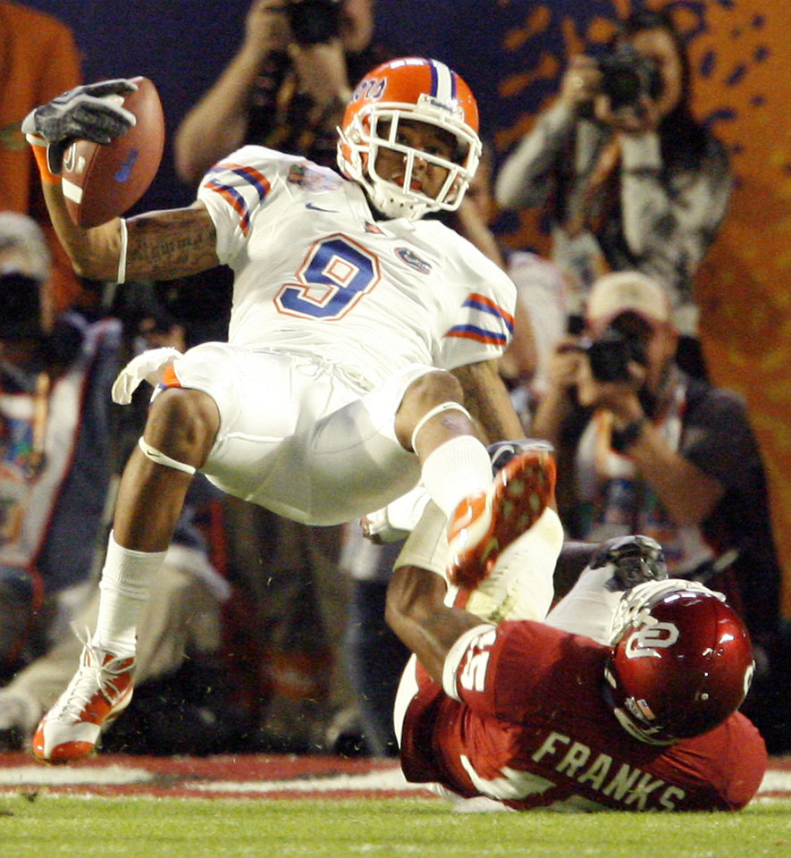 Photo - Florida's Louis Murphy (9) fall over Oklahoma's Dominique Franks (15) to score a touchdown during the first half of the BCS National Championship college football game between the University of Oklahoma Sooners (OU) and the University of Florida Gators (UF) on Thursday, Jan. 8, 2009, at Dolphin Stadium in Miami Gardens, Fla. 