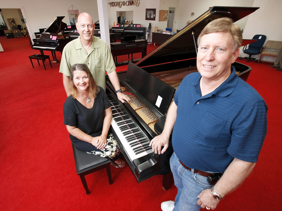 Albert Evans' children, Elaine Evans Walters, Phillip Evans, left, and Steve Evans surround a restored 1911 Baldwin piano at their late father's store at 4100 N MacArthur Blvd. Auctioneer Louis Dakil will sell the real estate and liquidate the inventory at auctions Saturday at his warehouse, 200 NW 114. Photo by Steve Gooch, The Oklahoman