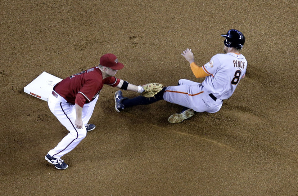 Photo - Arizona Diamondbacks' Aaron Hill tags out San Francisco Giants' Hunter Pence (8) on a steal attempt during the fourth inning of a baseball game, Sunday, June 22, 2014, in Phoenix. (AP Photo/Matt York)