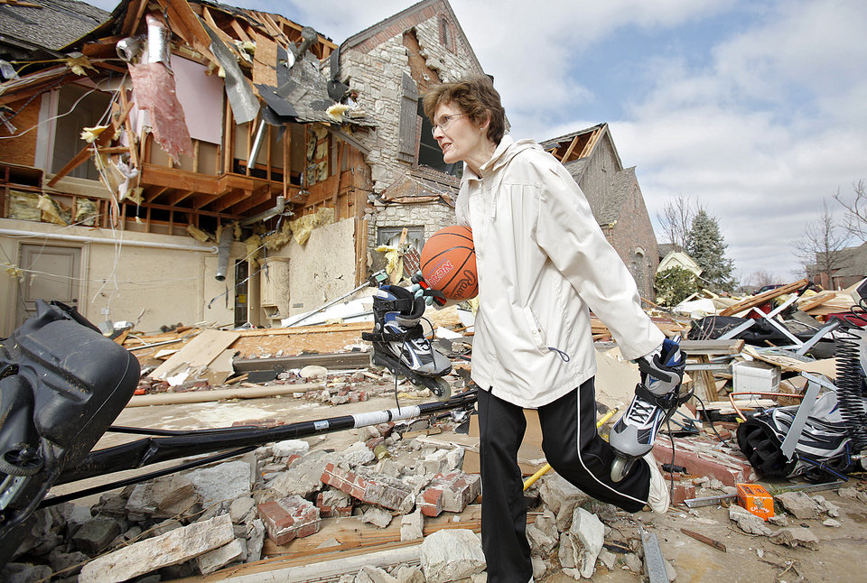 Photo - TORNADO / STORM / DAMAGE: Hazel Wright gather items from the damage at her daughter's home in the Oak Tree housing addition on Wednesday, Feb. 11, 2009, after a tornado hit the area on Tuesday in Edmond, Okla.  PHOTO BY CHRIS LANDSBERGER, THE OKLAHOMAN  ORG XMIT: KOD