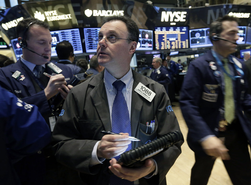 Trader Joseph Tarangelo, center, works on the floor of the New York Stock Exchange Tuesday, Jan. 22, 2013. Stocks are wavering in early trading on Wall Street as U.S. companies turn in a mixed batch of earnings reports. (AP Photo/Richard Drew)