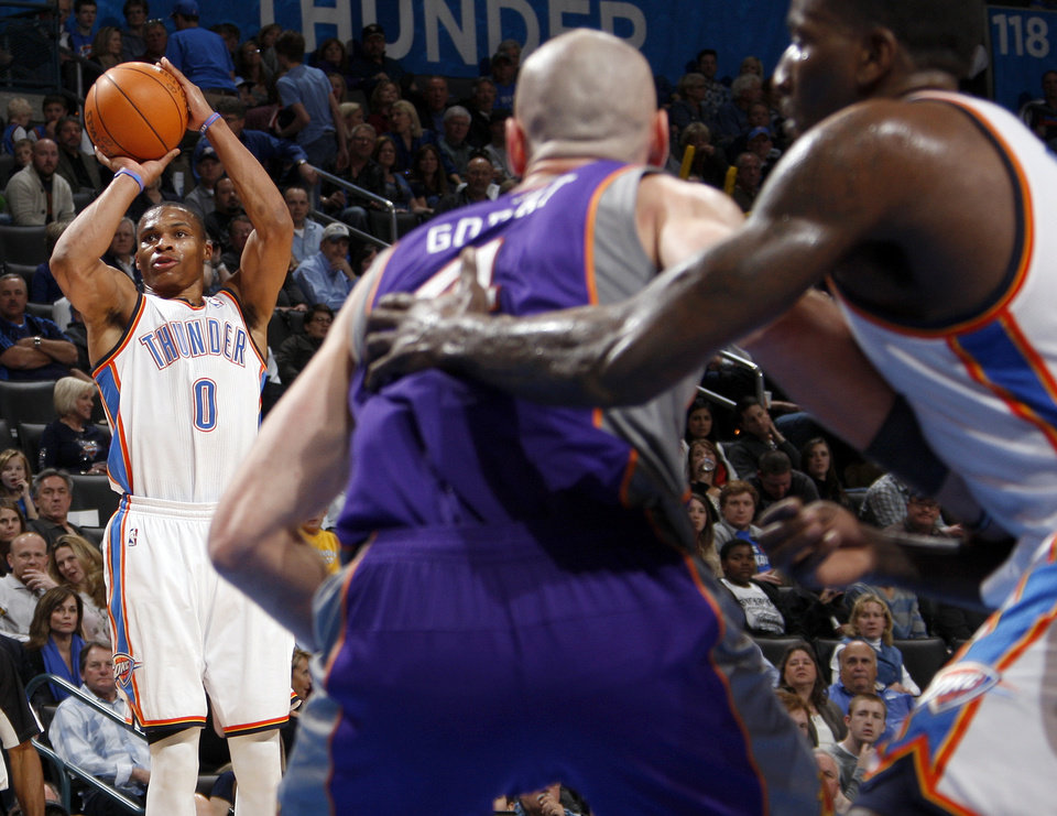 Photo - Oklahoma City's Russell Westbrook (0) takes a shot in the third quarter during the NBA basketball game between the Oklahoma City Thunder and Phoenix Suns at Chesapeake Energy Arena in Oklahoma City, Saturday, Dec. 31, 2011. At right are Marcin Gortat (4) of Phoenix and Oklahoma City's Kendrick Perkins (5). Oklahoma City won, 107-97. Photo by Nate Billings, The Oklahoman