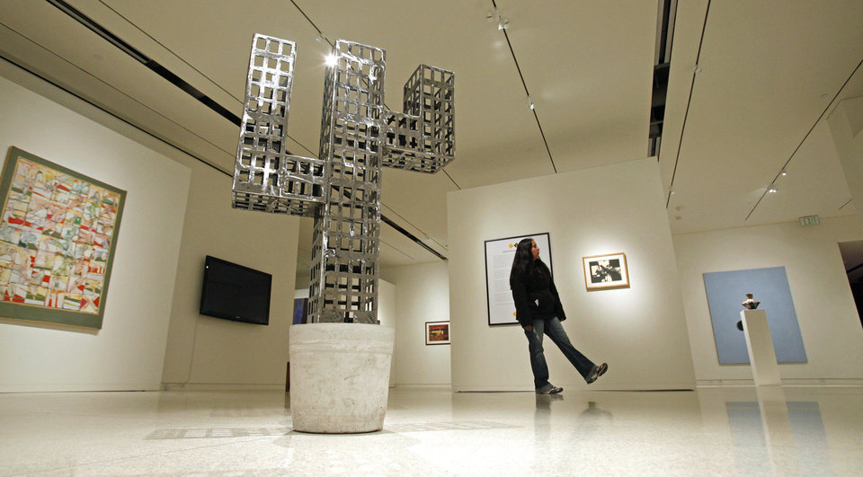 Photo - A visitor to the Fred Jones Jr. Museum of Art looks at School of Art and Art History students' work at a previous year's student art exhibition. Students will celebrate 100 years of annual student shows in January. OKLAHOMAN ARCHIVES  STEVE SISNEY