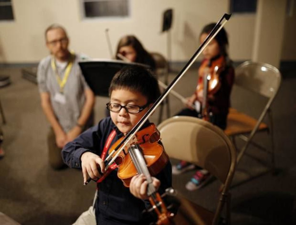 Photo - Jason Ngo, 9, a Kaiser Elementary School fourth grader, plays the violin during a recent practice session of the El Sistema Oklahoma youth orchestra.  SARAH PHIPPS - The Oklahoman