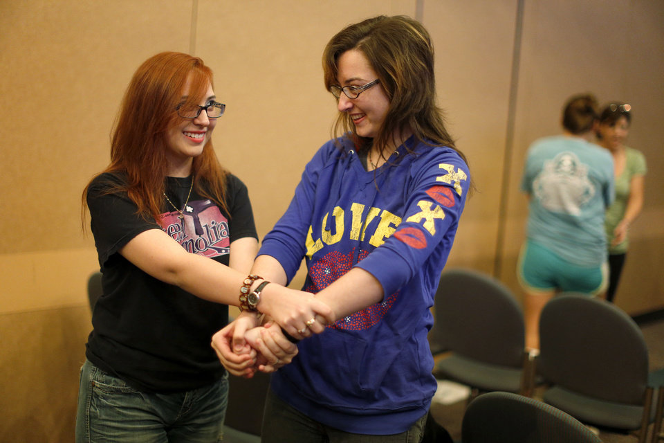 Photo - Alexandra Frechette, 17, and Heidi Henderson practice a self-defense hold at a recent