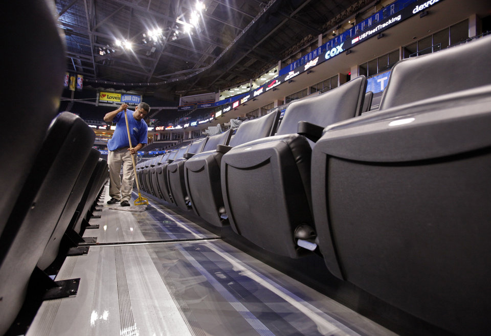 Photo - Gerardo Basquiec mops between seats in preparation for the first game of the NBA basketball finals at the Chesapeake Arena on Tuesday, June 12, 2012 in Oklahoma City, Okla. Photo by Steve Sisney, The Oklahoman  STEVE SISNEY