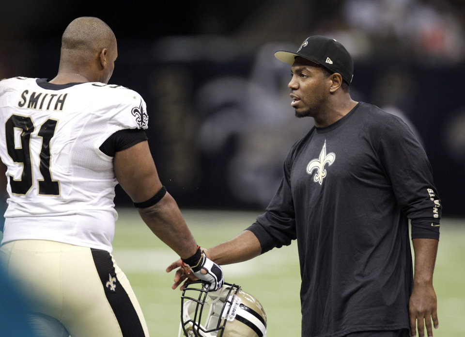 Photo -   New Orleans Saints defensive end Will Smith (91) shakes hands with linebacker Jonathan Vilma in the second half of an NFL football game against the Washington Redskins at Mercedes-Benz Superdome in New Orleans, Sunday, Sept. 9, 2012. The Saints won 40-32. (AP Photo/Matthew Hinton)