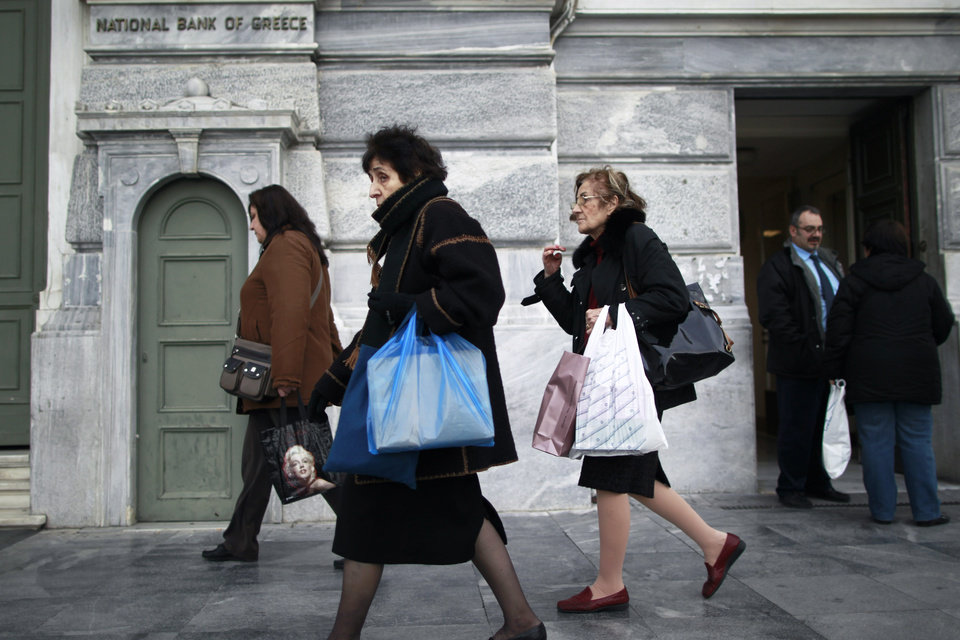 Photo - Athenians walk past a central Athens branch of  National Bank of Greece, the country's largest lender, Tuesday, Dec. 11, 2012. Greece was expected to announce later Tuesday the results of a bond buyback hoped to cut some 20 billion euros off the country's 340 billion euro debt load. Domestic lenders will contribute strongly in the European-funded buyback, which if successful will open the way for disbursement of a delayed international rescue loan payment. (AP Photo/Petros Giannakouris)
