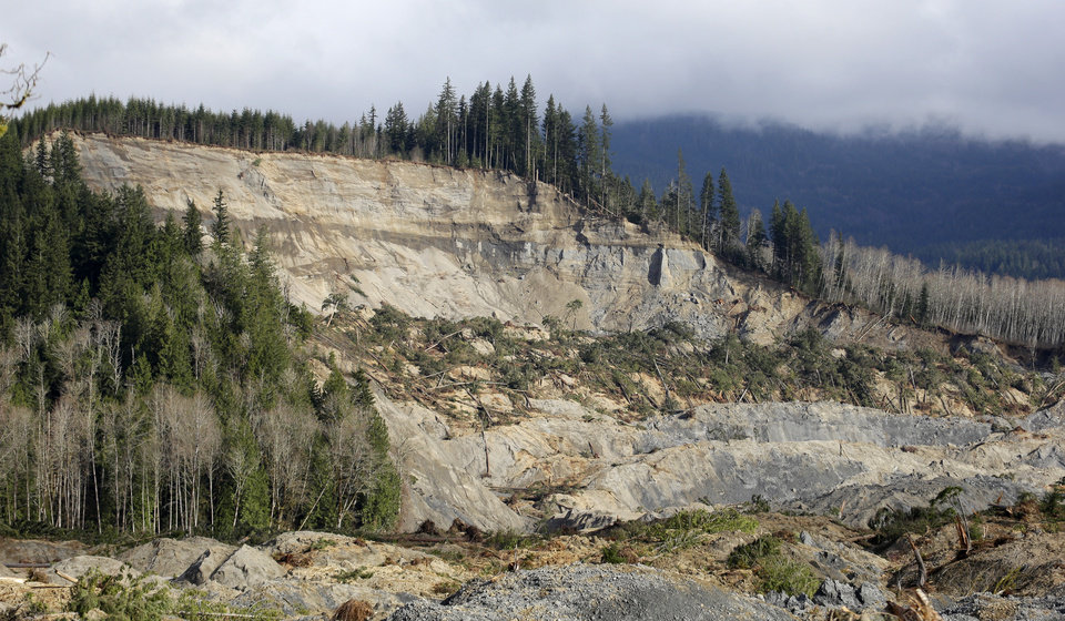 Photo - A now-barren hillside overlooks the valley below at the scene of a deadly mudslide, Wednesday, April 2, 2014, in Oso, Wash. Officials have so far confirmed the deaths of 29 people, although only 22 have been officially identified in information released Wednesday morning by the Snohomish County medical examiner's office. (AP Photo/Elaine Thompson)