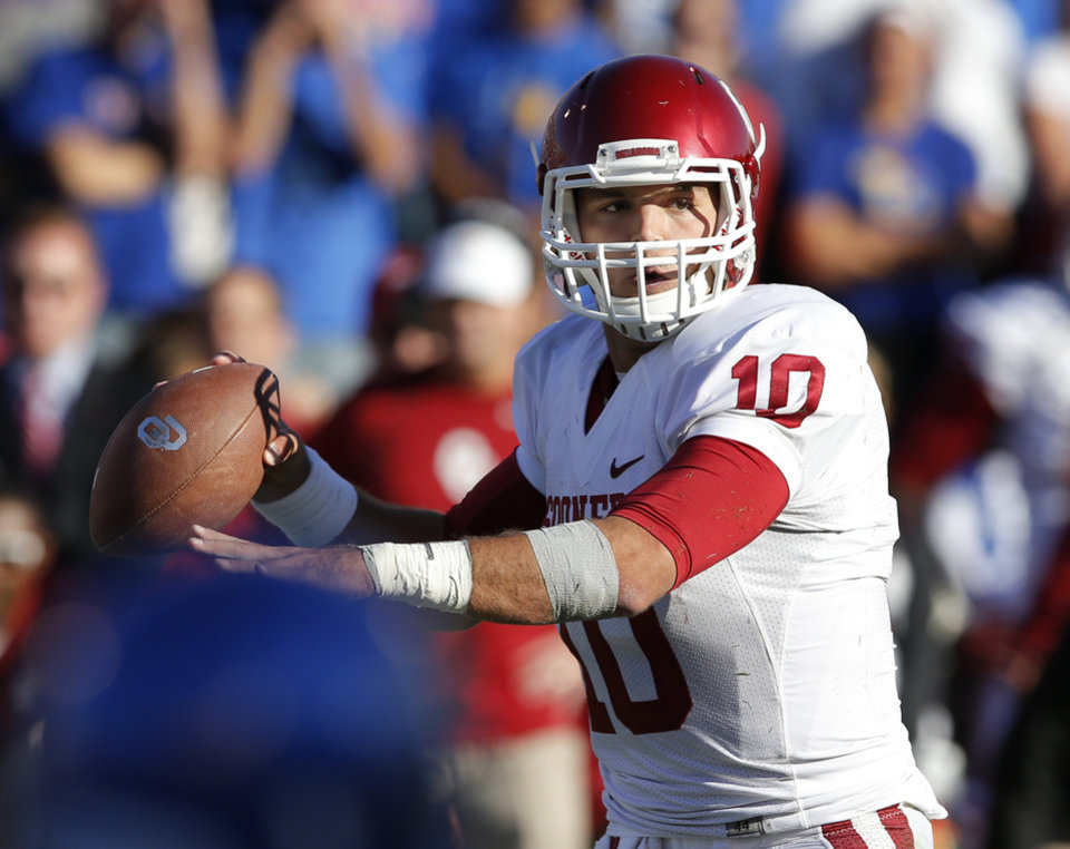 Photo - Oklahoma quarterback Blake Bell (10) passes to a teammate during the second half of an NCAA college football game against Kansas in Lawrence, Kan., Saturday, Oct. 19, 2013. Bell passed for 131 yards and two touchdowns. Oklahoma defeated Kansas 34-19. (AP Photo/Orlin Wagner)