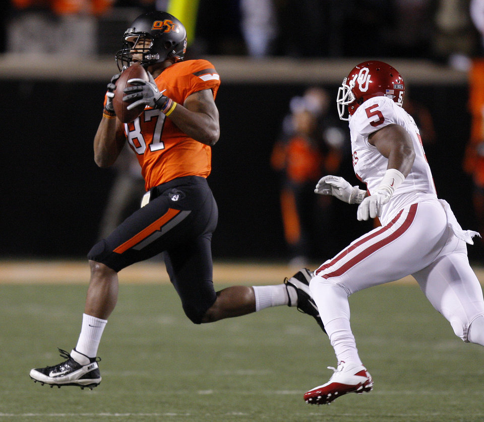Oklahoma State's Tracy Moore (87)catches a pass in front of Oklahoma's Joseph Ibiloye (5) during the Bedlam college football game between the Oklahoma State University Cowboys (OSU) and the University of Oklahoma Sooners (OU) at Boone Pickens Stadium in Stillwater, Okla., Saturday, Dec. 3, 2011. Photo by Bryan Terry, The Oklahoman