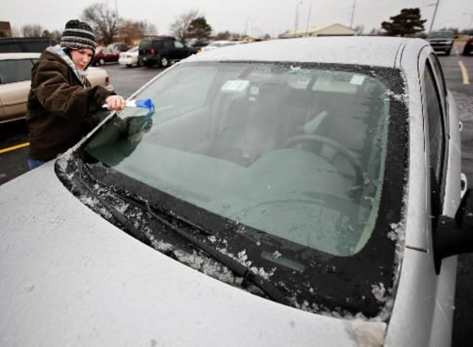 Photo - Amanda Knotts, nursing student from Yukon, removing ice from her windshield after classes were cancelled on the OSU OKC campus due to a winter storm moving through the metro in Oklahoma City Thursday, Jan. 28, 2010. Photo by Paul B. Southerland