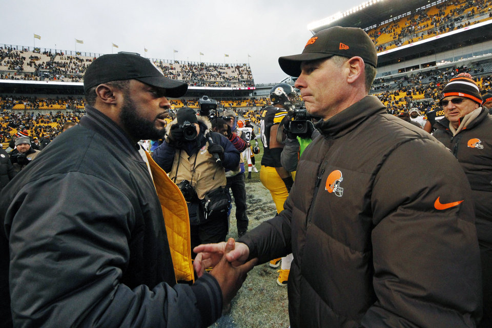 Photo - Pittsburgh Steelers head coach Mike Tomlin, left, shakes hands with Cleveland Browns head coach Pat Shurmur after the Steelers' 24-10 win in an NFL football game in Pittsburgh, Sunday, Dec. 30, 2012. (AP Photo/Gene J. Puskar)