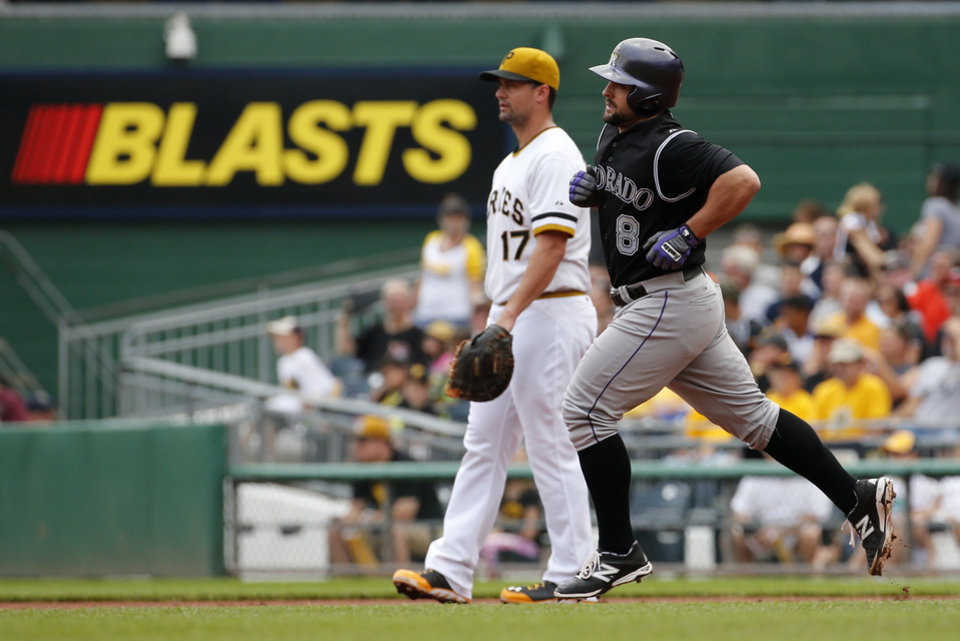 Photo - Colorado Rockies' Michael McKenry (8) rounds first past Pittsburgh Pirates first baseman Gaby Sanchez (17) after hitting a solo home run off Pittsburgh Pirates starting pitcher Jeff Locke during the second inning of a baseball game in Pittsburgh, Sunday, July 20, 2014. (AP Photo/Gene J. Puskar)