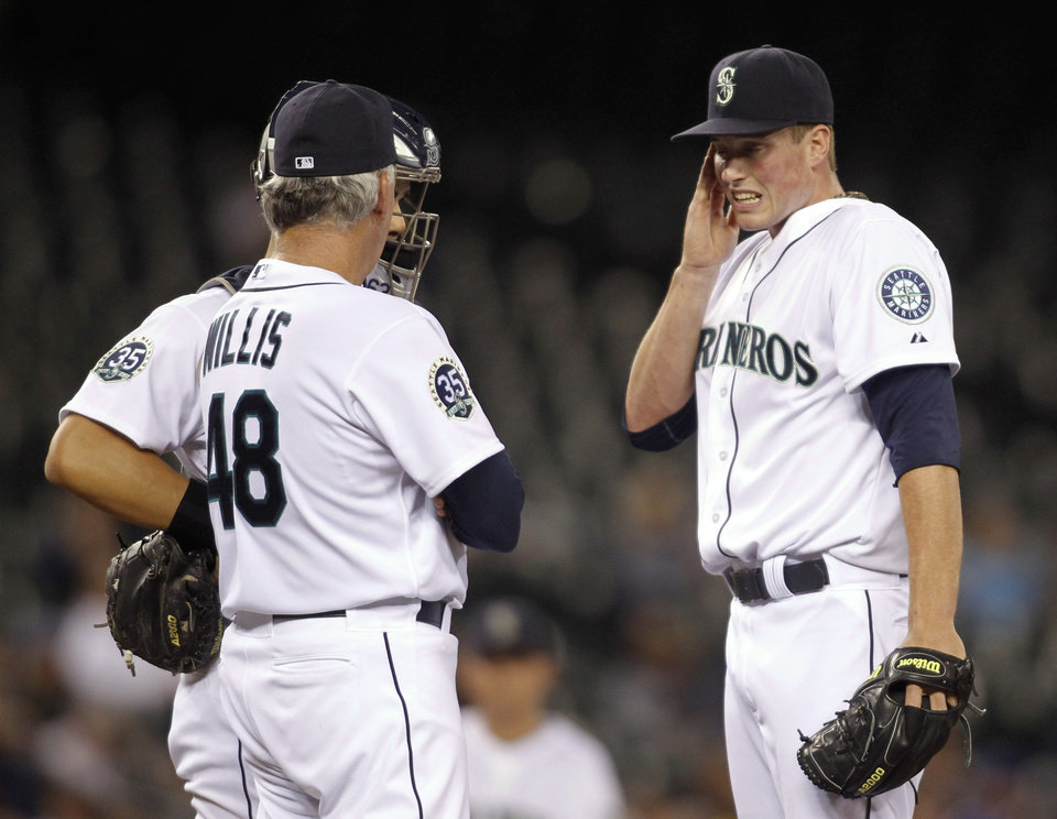 Photo -   Seattle Mariners relief pitcher Carter Capps wipes his face while talking with pitching coach Carl Willis during the sixth inning of a baseball game against the Oakland Athletics in Seattle on Saturday, Sept. 8, 2012. (AP Photo/John Froschauer)