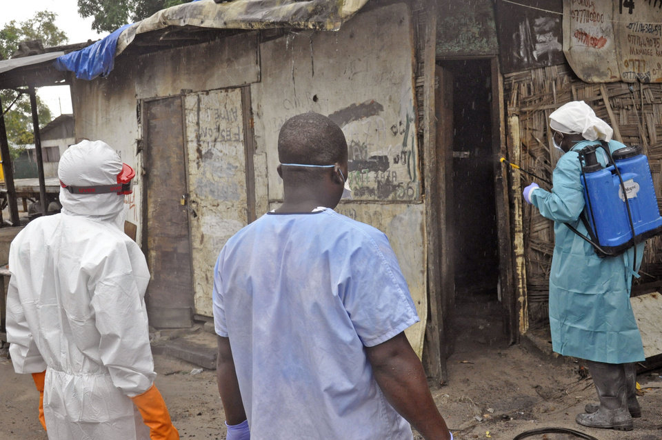 Photo - Liberian health workers spray disinfectant outside a house before entering and removing the body of a man that they believe died from the Ebola virus  in Monrovia, Liberia, Friday, Aug. 29, 2014.  The Ebola outbreak in West Africa eventually could exceed 20,000 cases, more than six times as many as are now known, the World Health Organization said Thursday. A new plan released by the U.N. health agency to stop Ebola also assumes that the actual number of cases in many hard-hit areas may be two to four times higher than currently reported.(AP Photo/Abbas Dulleh)