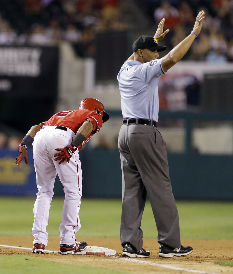 Photo - Los Angeles Angels' Erick Aybar dusts himself off on a triple as umpire C.B. Bucknor calls time in the sixth inning of a baseball game against the Tampa Bay Rays in Anaheim, Calif., Monday, Sept. 2, 2013. (AP Photo/Reed Saxon)