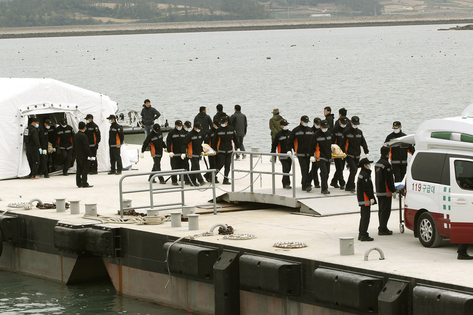 Photo - Emergency workers carry the bodies of passengers aboard the Sewol ferry which sank in the water off the southern coast, upon their arrival at a port in Jindo, South Korea, Tuesday, April 22, 2014. As divers continue to search the interior of the sunken ferry, the number of confirmed deaths has risen, with about 220 other people still missing. (AP Photo/Ahn Young-joon)