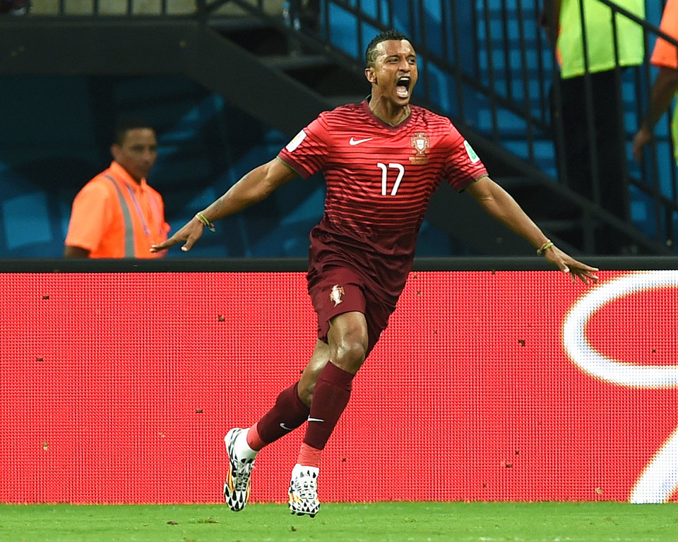 Photo - Portugal's Nani celebrates after scoring the opening goal during the group G World Cup soccer match between the USA and Portugal at the Arena da Amazonia in Manaus, Brazil, Sunday, June 22, 2014.  (AP Photo/Paulo Duarte)