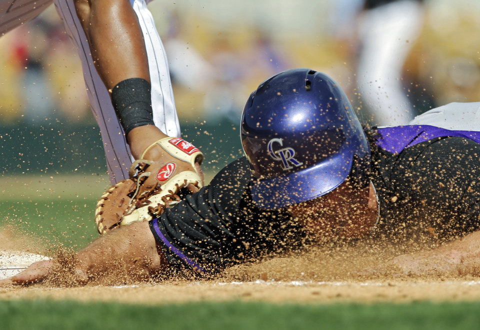 Photo - Colorado Rockies' Charlie Culberson dives back safely at first base on a pick-off attempt in the fifth inning of a spring exhibition baseball game against the Chicago White Sox on Tuesday, March 25, 2014, in Glendale, Ariz. (AP Photo/Mark Duncan)
