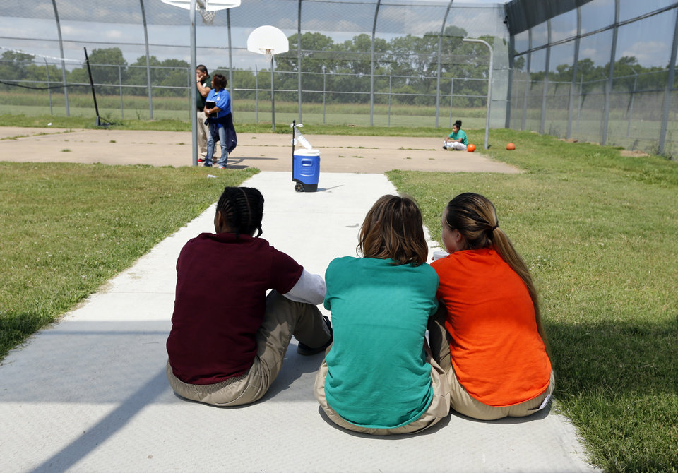 Photo -  Girls in state custody sit in the only outdoor space available to them, a fenced-in basketball court, at the Oklahoma Juvenile Center for Girls in Norman. The girls facility is operated by the Office of Juvenile Affairs. [Photo by Steve Sisney, The Oklahoman]