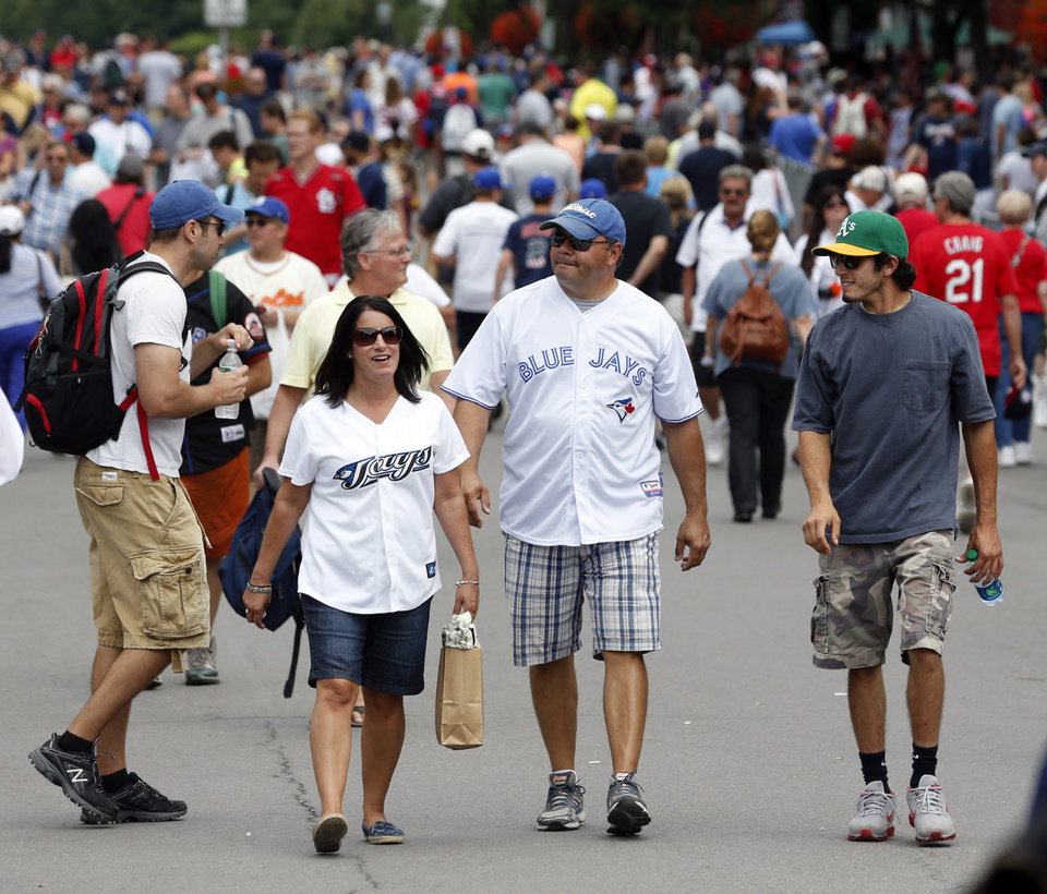 Photo - Baseball fans walk along Main Street on Saturday, July 26, 2014, in Cooperstown, N.Y. The Baseball Hall of Fame induction ceremony is Sunday. (AP Photo/Mike Groll)