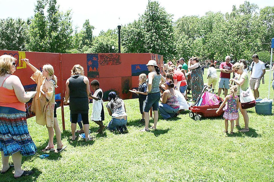 Participants at last year�s Luncheon on the Grass event paint on the children�s art wall at Lions Park in Norman. PHOTO PROVIDED