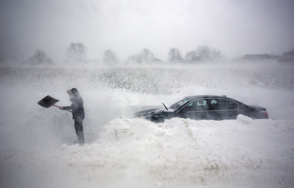 Photo - A woman digs out her car after it was blocked in by drifting snow during a blizzard, Saturday, Feb. 9, 2013, in Portland, Maine. The storm dumped more than 30 inches of snow as of Saturday afternoon, breaking the record for the biggest storm on record. (AP Photo/Robert F. Bukaty)